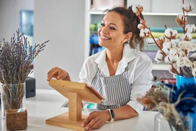 Affascinante signora in grembiule sorridente in un negozio di fiori