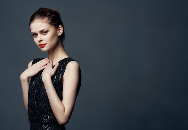 Affascinante signora in abito nero gesticolando isolato
