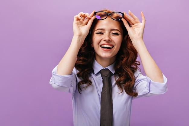 Affascinante signora in camicia blu che si toglie gli occhiali e ride