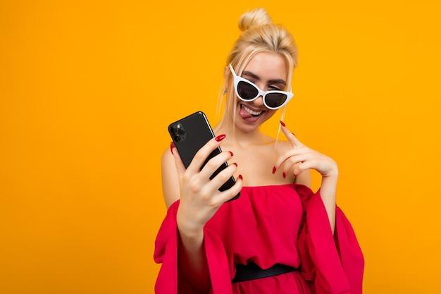 Affascinante signora in un vestito rosso in occhiali da sole sul viso tiene un telefono su un giallo
