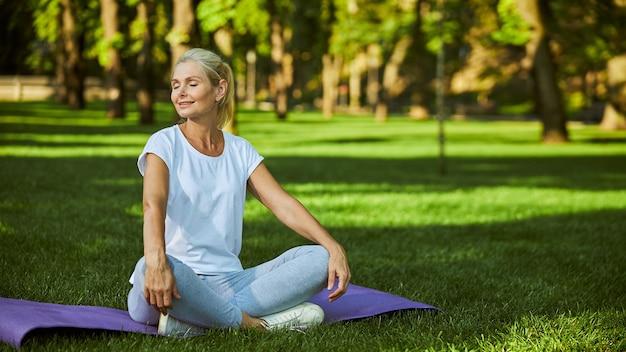 Affascinante signora in abbigliamento sportivo che chiude gli occhi e sorride mentre pratica lo yoga nel parco con erba verde