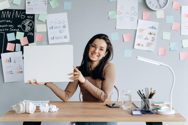 Affascinante signora su un muro di grigio, incollato con adesivi colorati sulla parete seduta alla scrivania