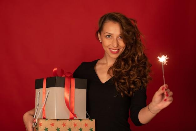 Affascinante signora con regali di festa e sorridente scintillante