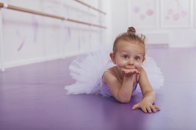 Affascinante piccola ballerina che soffia baci alla telecamera, sdraiato sul pavimento in classe di balletto