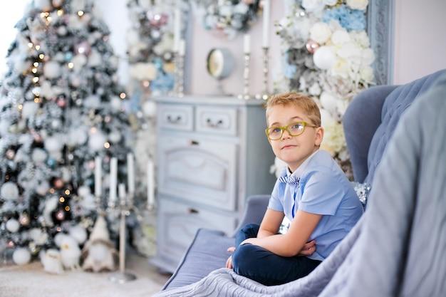 Affascinante piccolo ragazzo biondo in camicia blu con grandi occhiali seduto sul divano