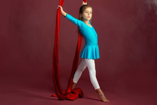Affascinante bambina in una tuta da ginnastica blu preparata per le prestazioni con un nastro rosso arioso