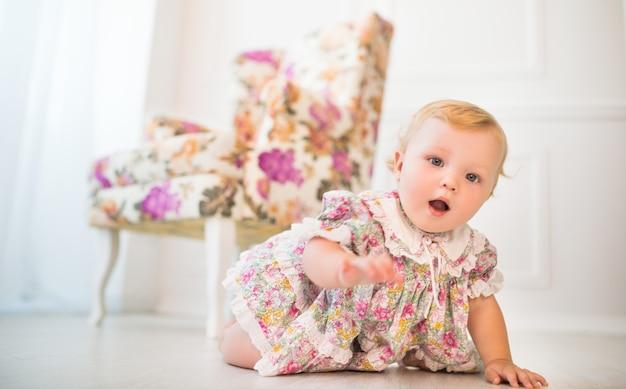 Affascinante bambina in abito floreale striscia sul pavimento di un bellissimo soggiorno elegante