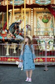 L'affascinante bambina vicino alla giostra tiene in mano un giocattolo di peluche contro nel parco di divertimenti