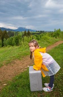 Affascinante bambina in una tuta antipioggia tiene una valigia in mano sulla strada per le montagne durante una nuvolosa giornata estiva