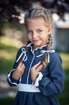 Affascinante bambina in un abito retrò che cammina in città in una soleggiata giornata estiva. la bambina indossa l'uniforme scolastica.