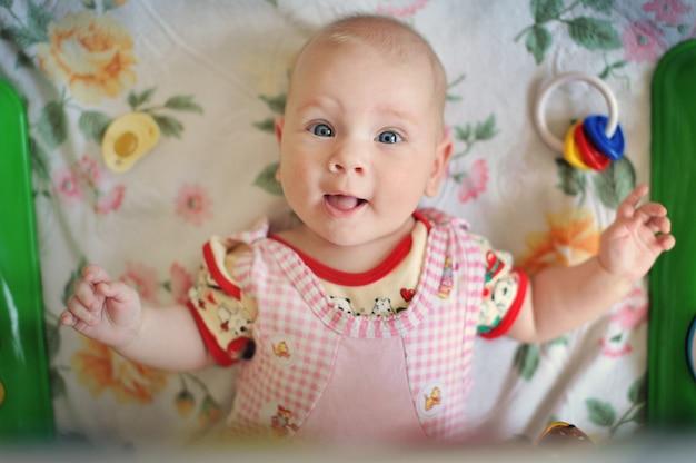 Affascinante bambina sorride e gioca con i giocattoli.