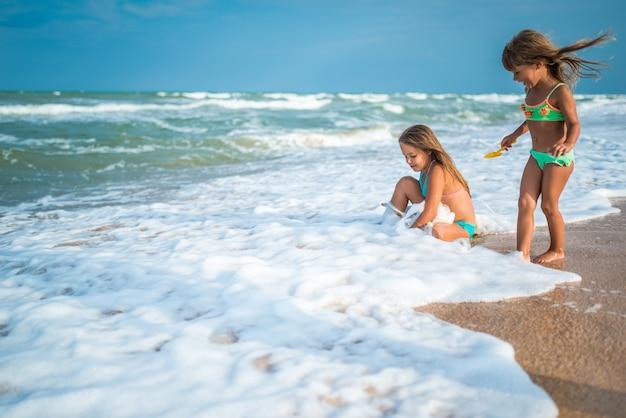 Affascinanti sorelle bambine nuotare e schizzare tra le onde del mare in una soleggiata giornata estiva calda durante le vacanze. concetto di divertimento e relax