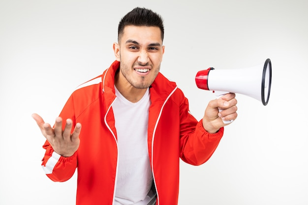 Uomo affascinante con un megafono in mano grida le notizie sugli sconti per gli acquisti su un bianco