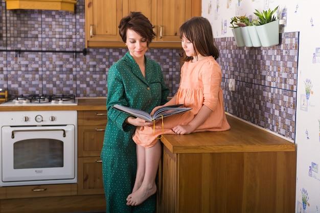 Affascinante madre sta mostrando le immagini in un libro alla sua graziosa piccola figlia a casa