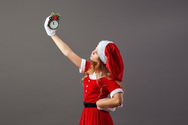 L'affascinante signora babbo natale vestita con l'abito rosso, il cappello di babbo natale e i guanti bianchi tiene un orologio che mostra le cinque meno dodici nella sua mano alzata. vigilia di natale .