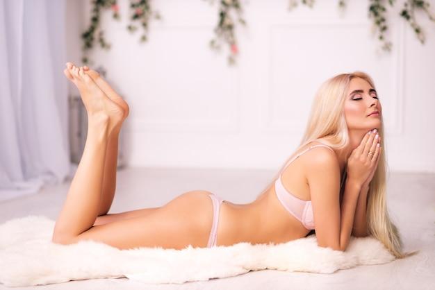 Affascinante giovane donna mistica in lingerie con lunghi capelli bianchi giace sul pavimento