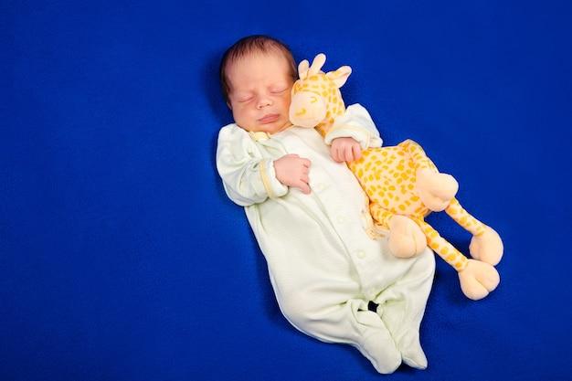 Affascinante neonato sdraiato su una coperta blu con giraffa giocattolo