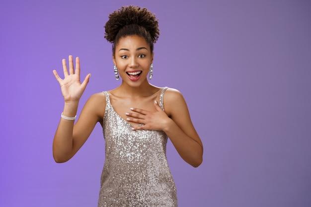 Affascinante e simpatica giovane donna afro-americana elegante incontra una persona familiare saluto alza la mano agitando la mano premendo il palmo del petto sorridendo ampiamente dire il nome, giurando di dire la verità, promettendo di non mentire.