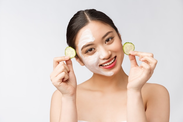 Donna piacevole affascinante che applica crema sulla mezza faccia
