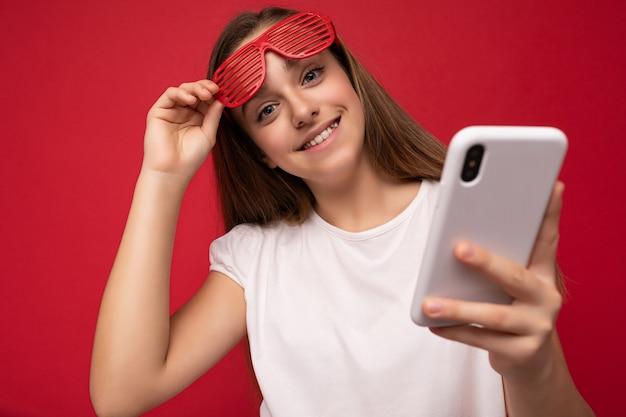 Affascinante ragazza positiva che indossa una maglietta bianca e occhiali rossi