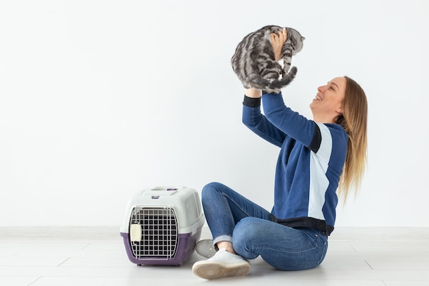 Affascinante giovane donna positiva tiene tra le mani il suo bellissimo gatto scozzese grigio piega seduto sul pavimento in un nuovo appartamento. concetto di animale domestico. copyspace