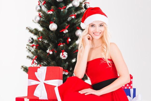 Affascinante giovane donna positiva con cappello di babbo natale seduto con regali vicino all'albero di natale su sfondo bianco