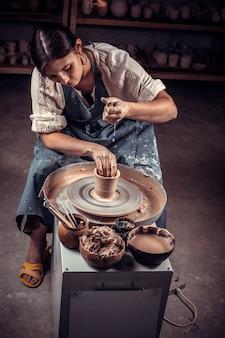 Un affascinante vasaio professionista crea una nuova ceramica dall'argilla su un tornio da vasaio
