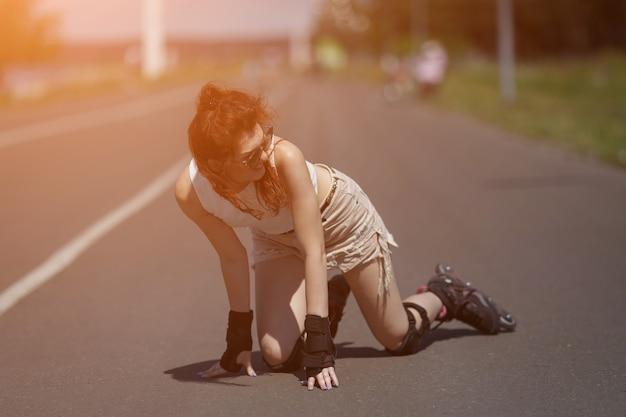 Affascinante ragazza dai capelli rossi in occhiali da sole e equipaggiamento protettivo cavalca su pattini a rotelle e cade per strada in una giornata di sole, luce solare