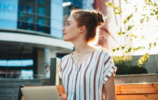 Affascinante ragazza dai capelli rossi con le lentiggini che guarda lontano mentre è seduto su una panchina in città