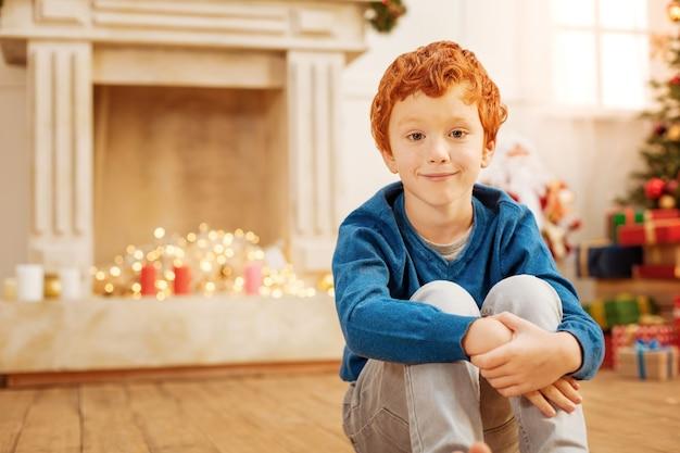 Affascinante ragazzo dai capelli rossi con un leggero sorriso sul viso mentre aspetta che la sua famiglia si svegli e apra insieme i regali di natale.