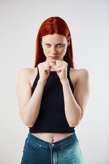 Affascinante ragazza dai capelli lunghi rossa vestita con top nero e jeans tiene le mani a pugno
