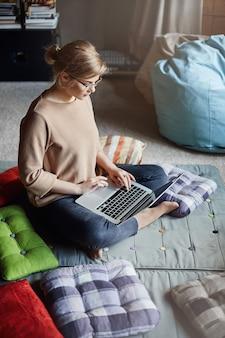 Affascinante ragazza caucasica rilassata con gli occhiali con i capelli biondi, seduta sul pavimento con i piedi incrociati, tenendo il laptop mentre si lavora con il notebook o la messaggistica, guardando video in internet.