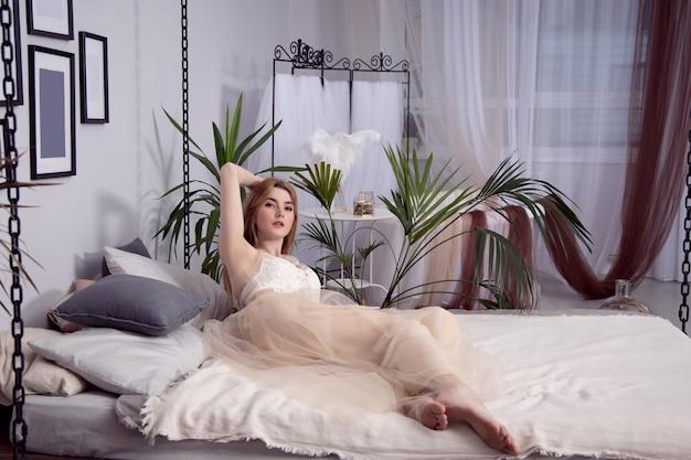 Affascinante ragazza sexy in una bella vestaglia è sdraiata su un grande letto in camera da letto