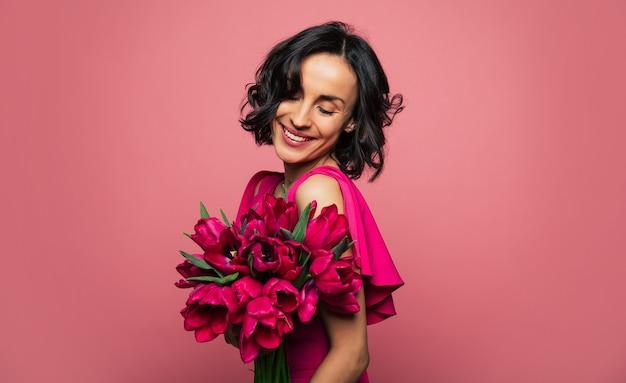 Sorriso affascinante. foto ravvicinata di una ragazza felice in un vestito elegante, che tiene in mano un mazzo di tulipani e lo guarda con un ampio sorriso.