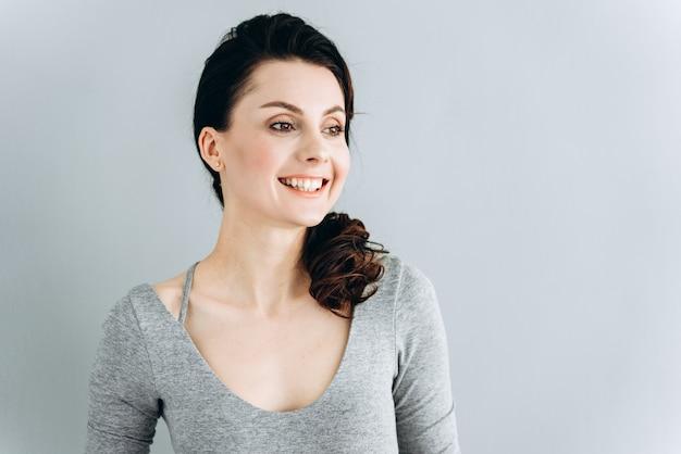 Affascinante, sorridente ragazza bruna su un muro grigio, guardando lontano.