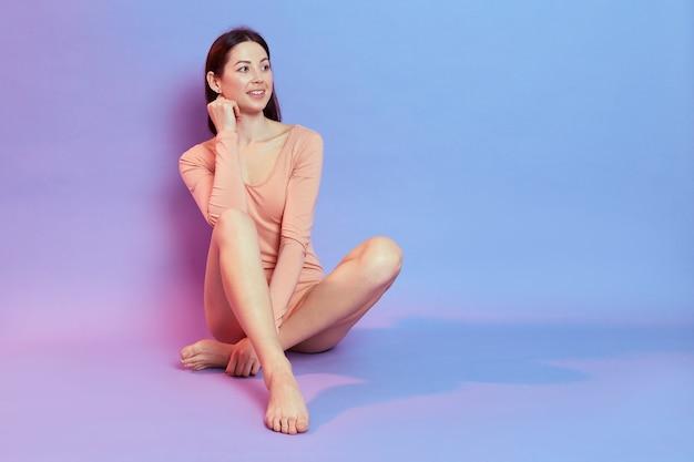 Affascinante signora dai capelli scuri sorridente indossa una tuta beige seduta sul copyspace del pavimento per la pubblicità, isolata sul muro blu con luce al neon rosa.
