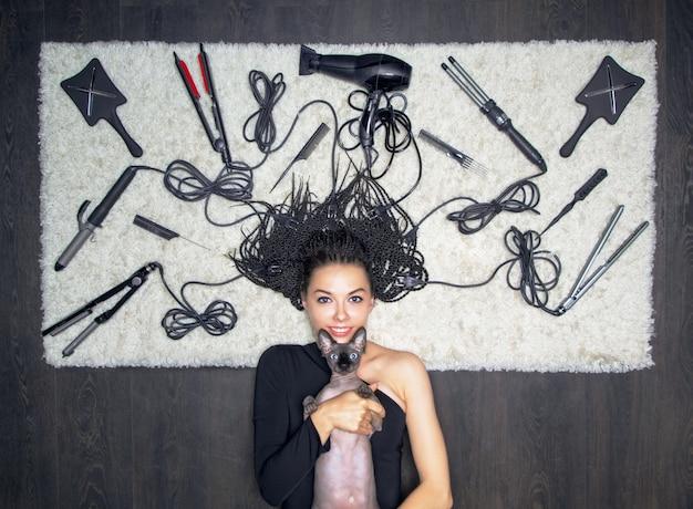Affascinante ragazza sorridente che abbraccia una sfinge sullo sfondo di un numero enorme di forniture di parrucchiere