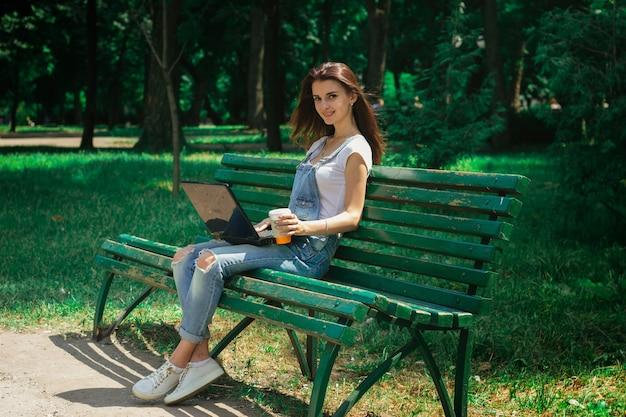 L'affascinante donna sorridente con un laptop nelle mani di seduta su una panchina