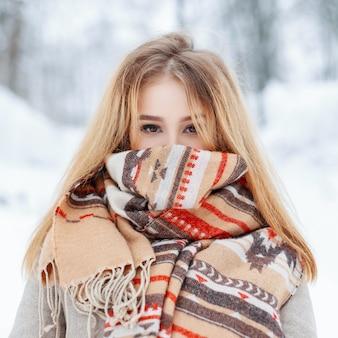 Affascinante giovane donna alla moda con gli occhi marroni in un cappotto vintage grigio alla moda in guanti caldi in un parco innevato di inverno. bella ragazza alla moda con una sciarpa di lana sul viso in una fredda giornata invernale.