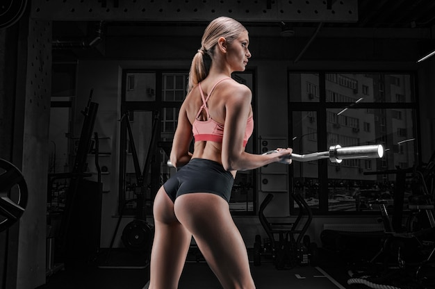 Affascinante atleta alto in posa in palestra con un bilanciere in mano. vista posteriore. il concetto di sport, bodybuilding, fitness, aerobica, stretching.