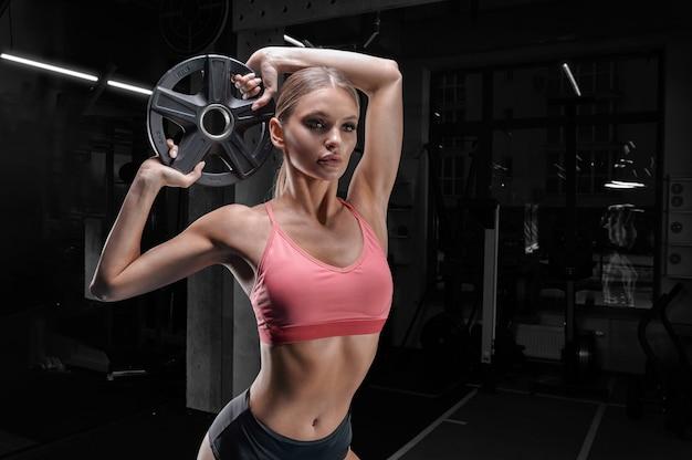Affascinante atleta alto in posa in palestra con un piatto di peso. il concetto di sport, bodybuilding, fitness, aerobica, stretching.