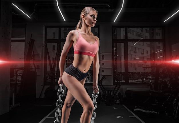 Affascinante sportiva alta in posa in palestra con catene.