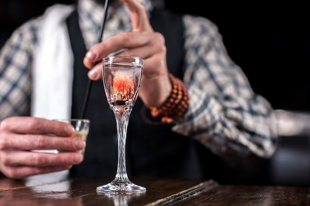 Affascinante tapster pone gli ultimi ritocchi su un drink dietro il bancone