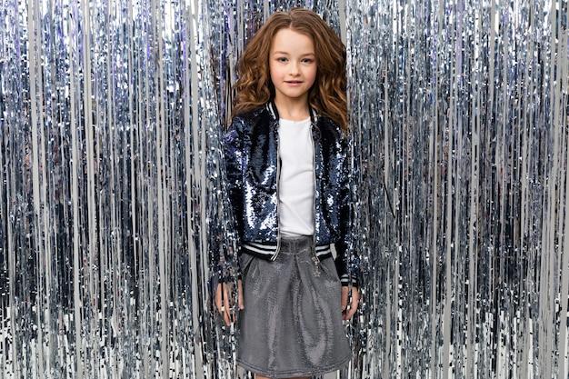Affascinante ragazza adolescente a una festa sullo sfondo di tinsel.