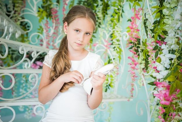Affascinante ragazza adolescente in un abito romantico bianco in posa ai fiori con la scarpa in mano