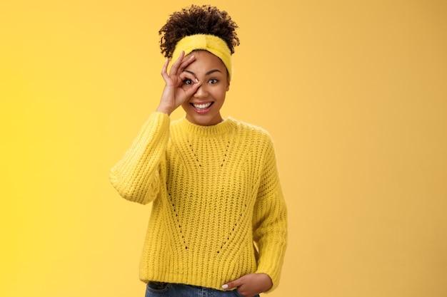 Affascinante ragazza afro-americana femminile tenera mostra cerchio sull'occhio ok gesto ok guardare fortunato felicemente sorridente soddisfatto impressionato in attesa eccitazione amici di viaggio, sfondo giallo.