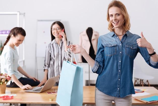 Affascinante donna allegra che tiene una grande borsa blu con un oggetto per il suo cliente e che mostra un gesto di pollice in alto, mentre i suoi colleghi sono impegnati in background