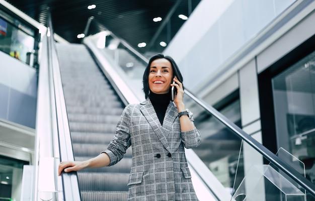Una donna affascinante con una giacca a scacchi scende le scale mobili mentre parla al telefono.
