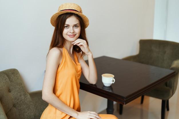 Affascinante donna in un vestito in un caffè e un cappello