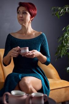Affascinante donna in abito da sera elegante e acconciatura luminosa con una tazza di caffè caldo